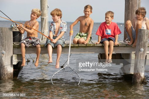 Five boys (5-13) sitting on jetty fishing, one holding net in water : Stock Photo