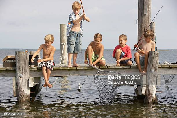 Five boys (5-13) sitting on jetty fishing, one standing up