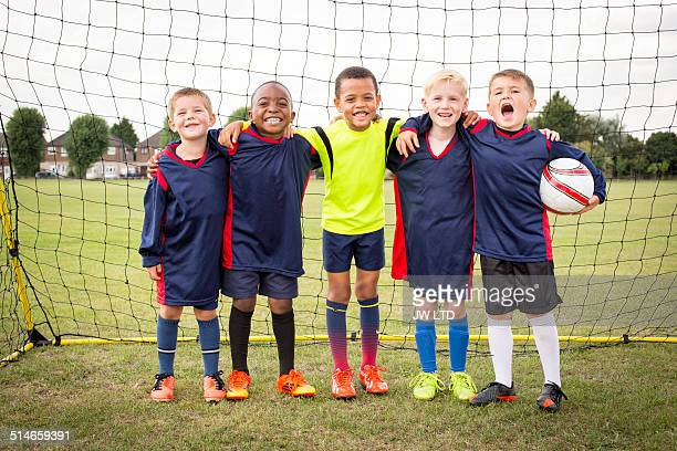 Five boys standing in football goal