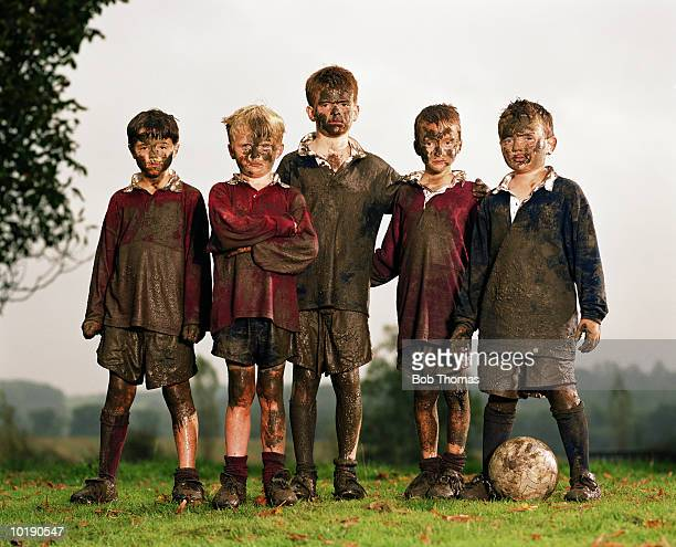 Five boys (8-10) with football, covered in mud, portrait