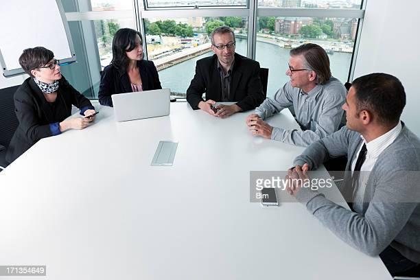 Cinq hommes d'affaires réunion à table dans la salle de conférence