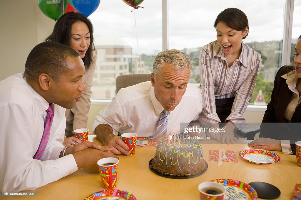 Five businesspeople celebrating birthday, mature man blowing candles : Stock Photo