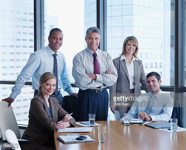 Five businesspeople in a boardroom looking at camera