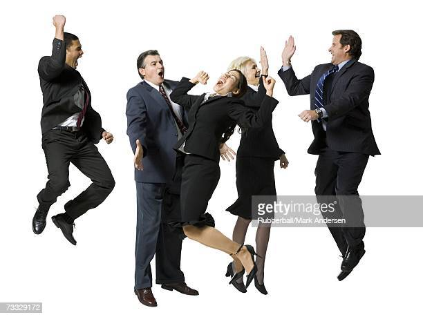 Five businesspeople leaping and smiling