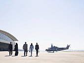 Five businesspeople walking to helicopter
