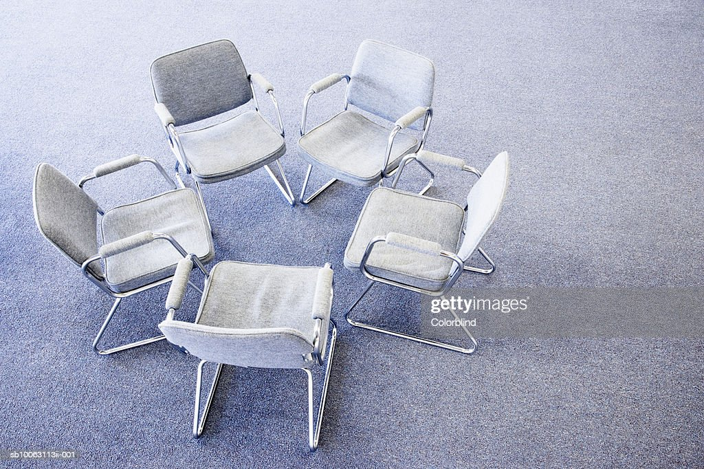 Five chairs in circle on office floor, elevated view : Stock Photo