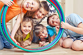 Five cheerful kids looking through hula hoops