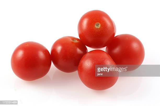 Five cherry tomatoes over a white background