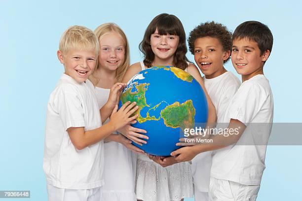 Cinco hijos sosteniendo un globo en el interior