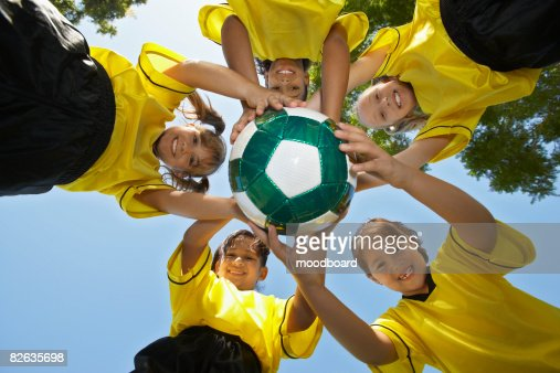 Five children (7-9 years) holding soccer ball, view from below, portrait : Stock-Foto