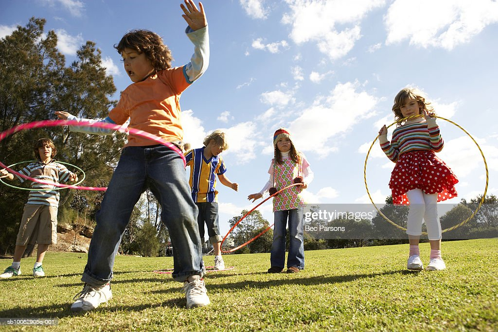 Five children (7-12) playing with plastic hoops in park : Stock Photo