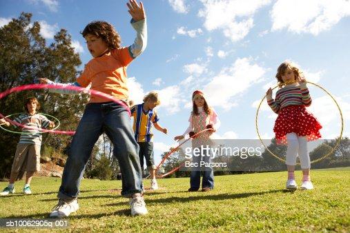 Five children (7-12) playing with plastic hoops in park : Foto de stock