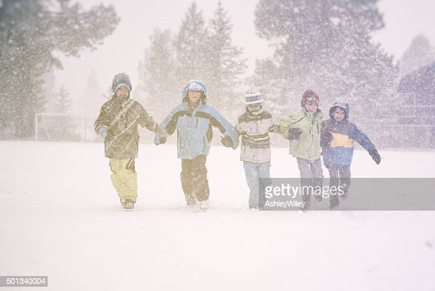 Five children running in a snow storm at school