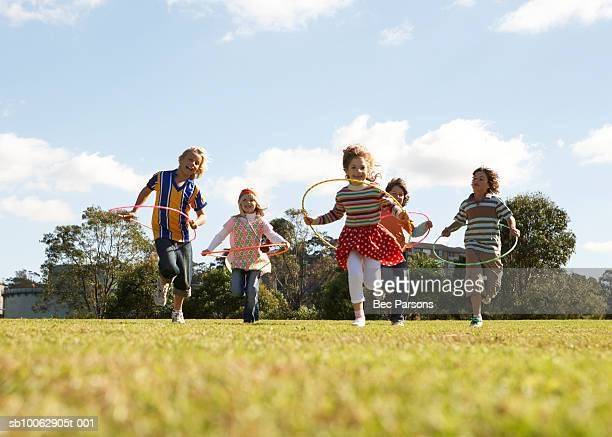 Five children (7-11) running with plastic hoops in park (surface level)