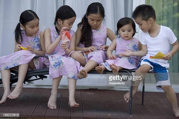 Five children sitting together on a chaise lounge making paper airplanes