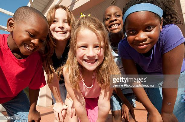 Five children smiling in front of the camera outdoors