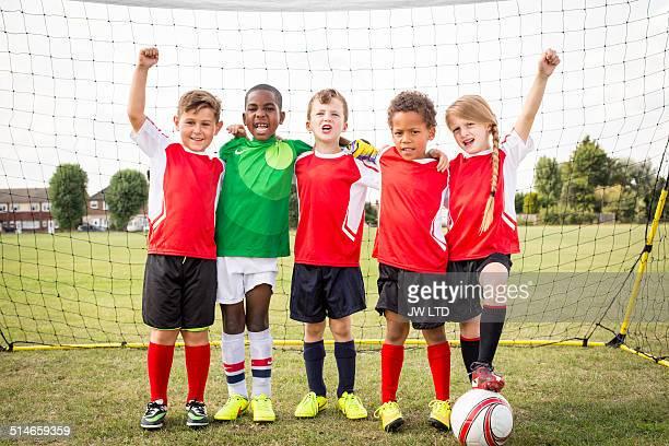 Five children standing in football goal
