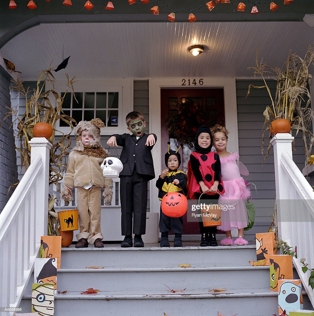 Five children standing on porch, wearing Halloween costumes, portrait