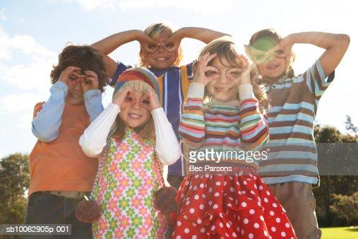Five children (7-12) with fingers over eyes, portrait (lens flare) : Foto de stock