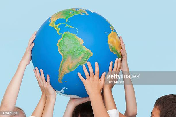 Five children's hands indoors touching a globe