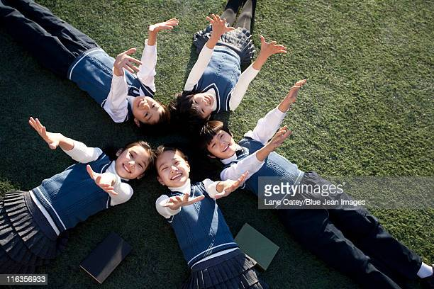 Five classmates lying in a star shape on grass