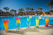 Five cocktail drinks by a tropical hotel resort swimming pool in summer