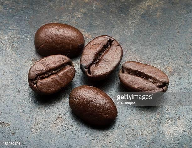 five coffee beans on steel
