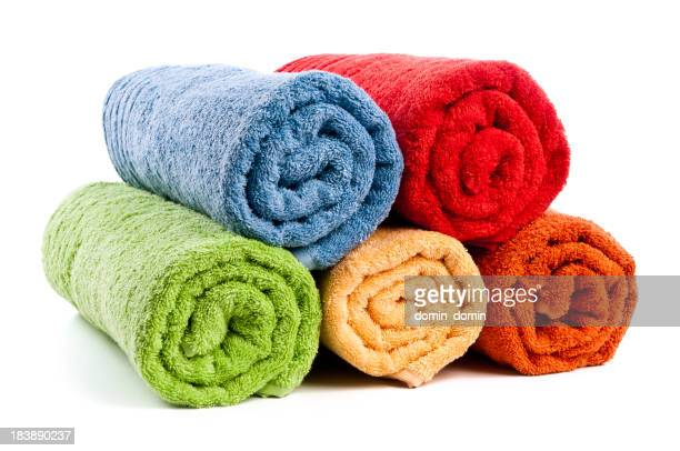 Five different colored rolled towels on white