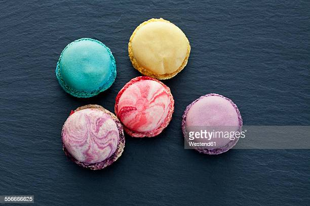 Five different macarons on slate