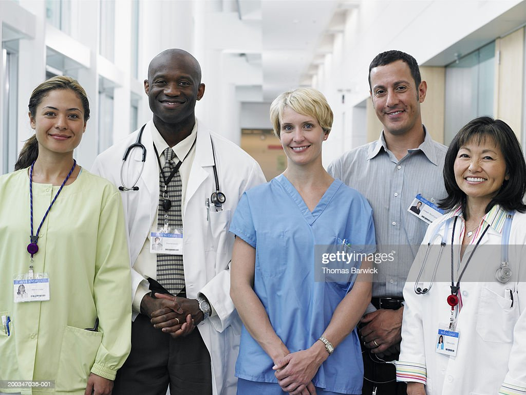 Five doctors and nurses standing in hospital corridor, portrait : Stock Photo