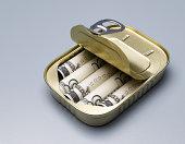 Five dollar bills in sardine can with open lid, studio shot