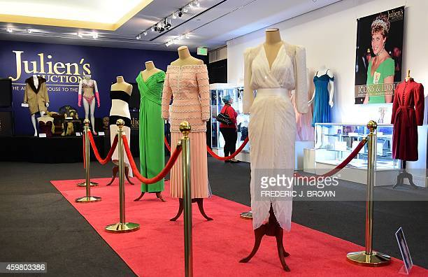 Five dresses worn by the late Princess Diana four on a red carpet and one beside her poster are displayed at Julien's Auction House in Beverly HIlls...