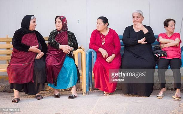 Five elderly ladies sitting on bench