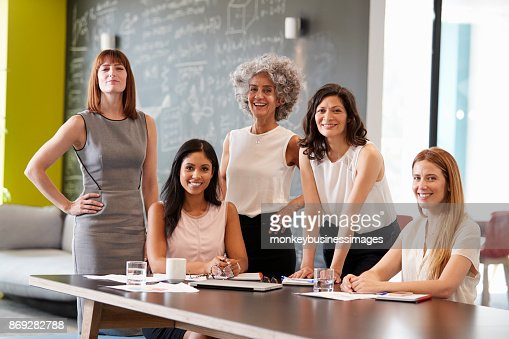 Five female colleagues at a work meeting smiling to camera : Stock Photo