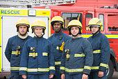Five firefighters standing by fire engine wearing helmets