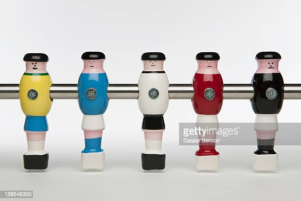 Five foosball figurines wearing different uniforms