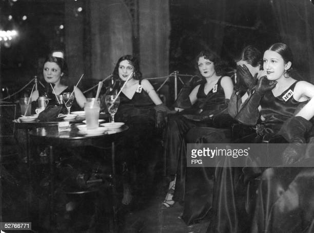 Five French taxi girls in black satin evening gowns sit and wait for customers at a nightclub Paris 1920s Taxi girls or taxi dancers are so named...
