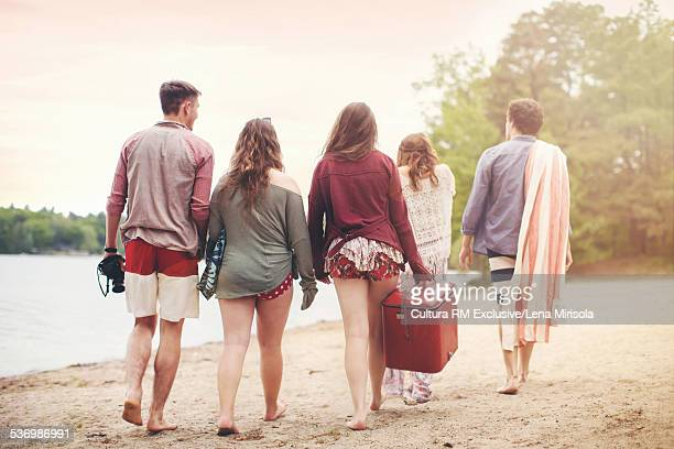 Five friends carrying cool box on beach