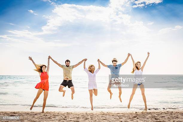 Five Friends On The Beach Jumping