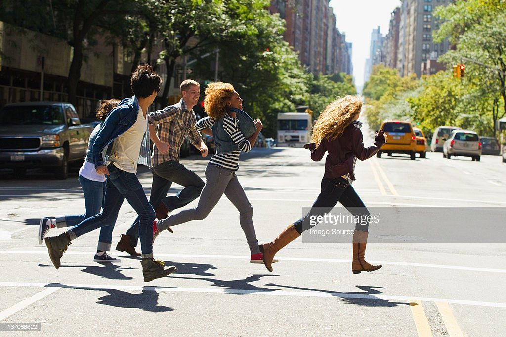 Five friends running through city street : Stock Photo