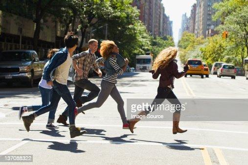 Five friends running through city street : Foto de stock