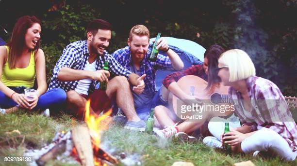 Cinq amis assis à côté de feu de camp et de la chanson chanter