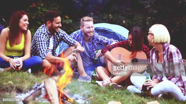 Five friends sitting next to campfire and singing song
