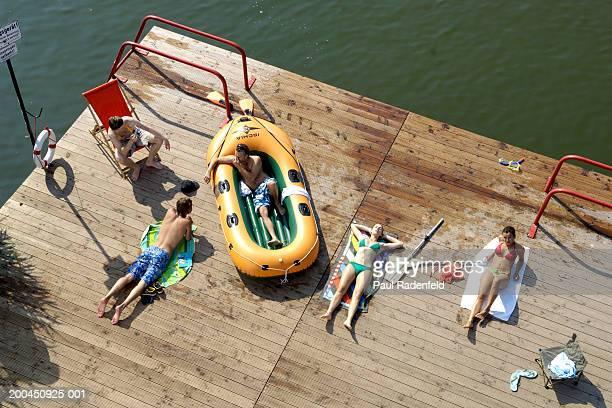 Five friends sunbathing on pier by lake, elevated view