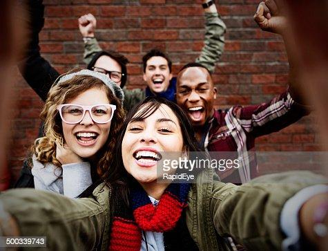 Five friends take happy, smiling selfie
