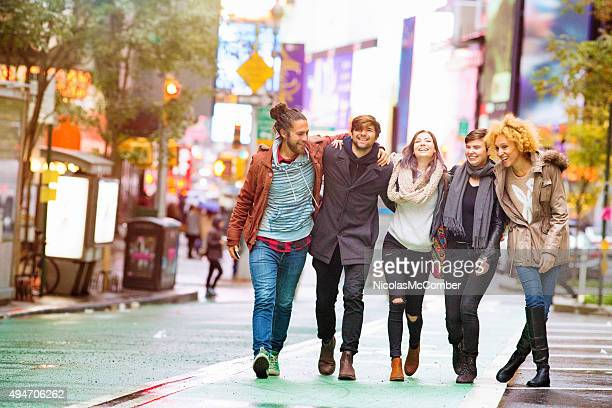 Five friends walking happy in Manhattan wet Autumn day