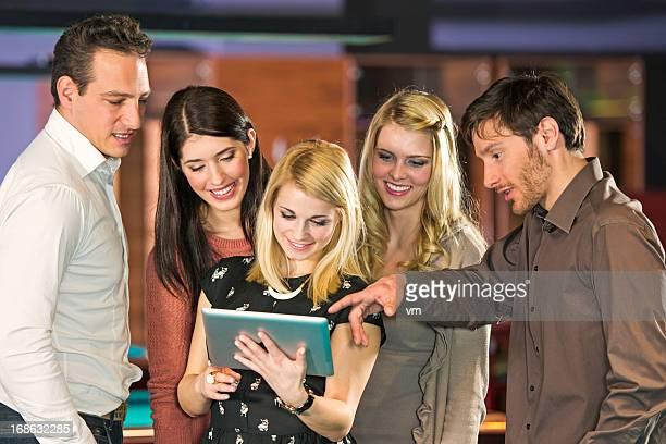 Cinq amis regardant Tablette numérique
