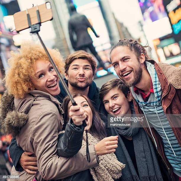 Five friends with selfiestick in New York street after rain.