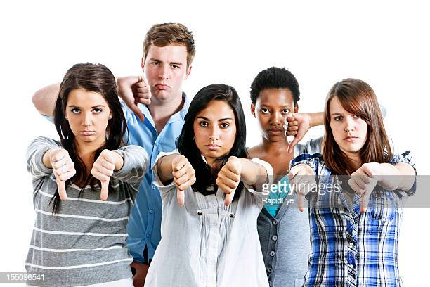 Five frowning young people show disapproval with thumbs down