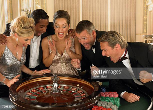 Five gamblers anticipating win at Roulette table